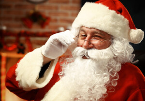 Portrait of happy Santa Claus holding Christmas letter